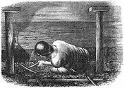 Miner working a seam with a pick 'scuffling' out the coal. Pit props and safety lamp. Wood engraving, 1864