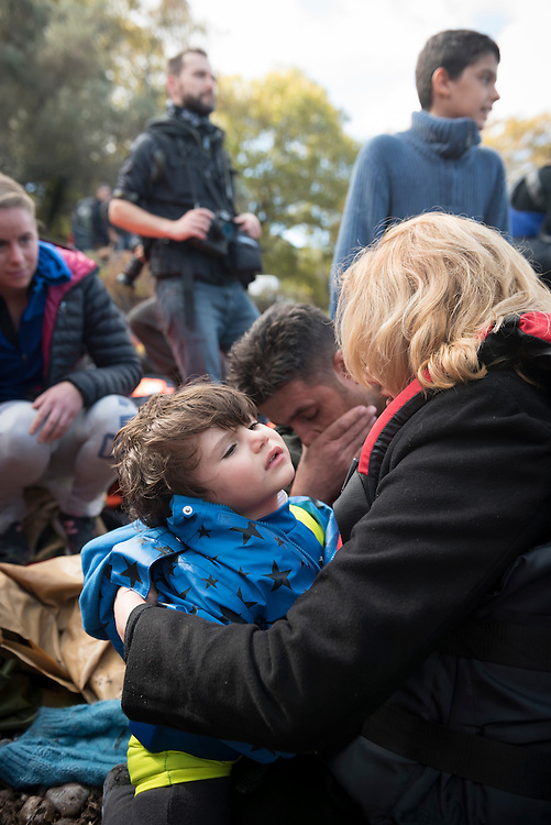Near the town of Skala Sikamineas on the Greek island of Lesbos, a husband, wife, and their child sit and kneel on the beach overcome with emotion, moments after arriving in a crowded inflatable boat from Turkey. In the background is a photographer (center) and a volunteer from Norway (left)