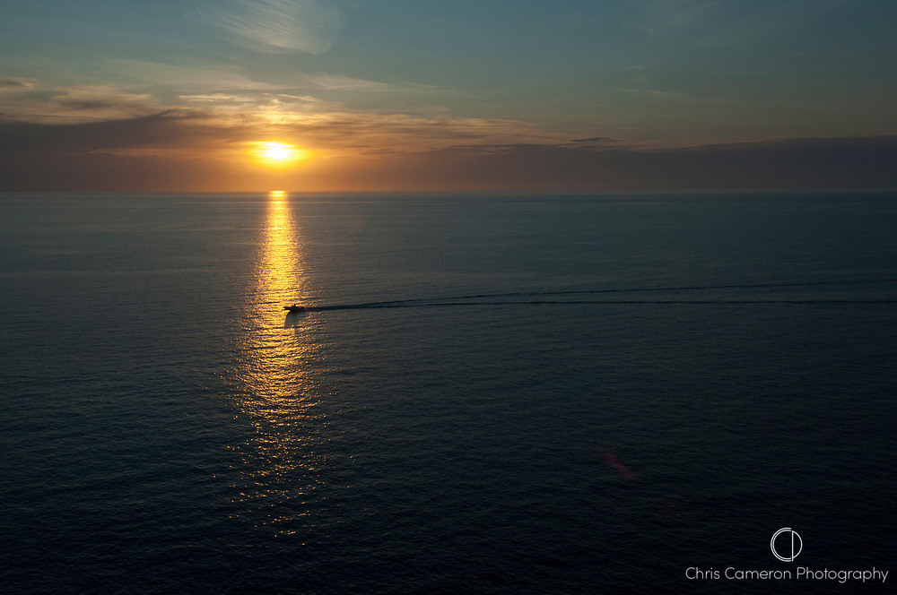 A small boat heads back to port at sunset. Soller, Mallorca, Spain