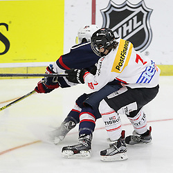 COBOURG, - Dec 16, 2015 -  Game #7 - United States vs Switzerland at the 2015 World Junior A Challenge at the Cobourg Community Centre, ON. Spenser Young #12 of Team United States and Kaj Suter #7 of Team Switzerland battle for the puck during the first period. (Photo: Tim Bates / OJHL Images)