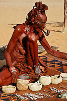 Portrait of older Himba woman smoking a pipe on a rug with baskets and jewelry. Fine art photography prints, wall art, and stock images.