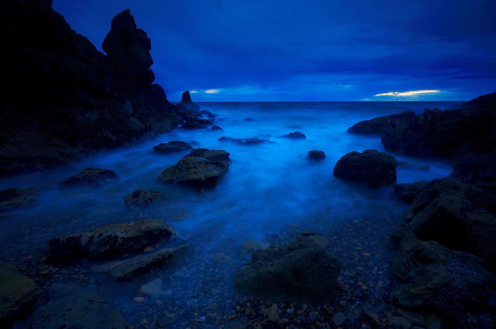Rock formations in Corona Del Mar, CA during a rainy evening.