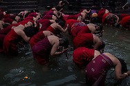 — The devotees take a holy bath to purify their bodies and spirits, an essential daily ritual for sanctifying the commencement of another day of worship.