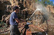 Tim Lukinuk of Amethyst Mine Panorama, uses high-pressure water hose to strip rock face and extract amethyst from his family's mine, largest deposit in Canada; Dorion, Ontario.