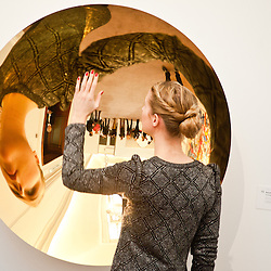A Sotheby's employee poses in front of an untitled work by Anish Kapoor during the press preview of the Sotheby's forthcoming February sales of Impressionist & Modern Art and Contemporary Art in London, including works by Picasso, Bacon, Monet, Richter, Miró, Basquiat.