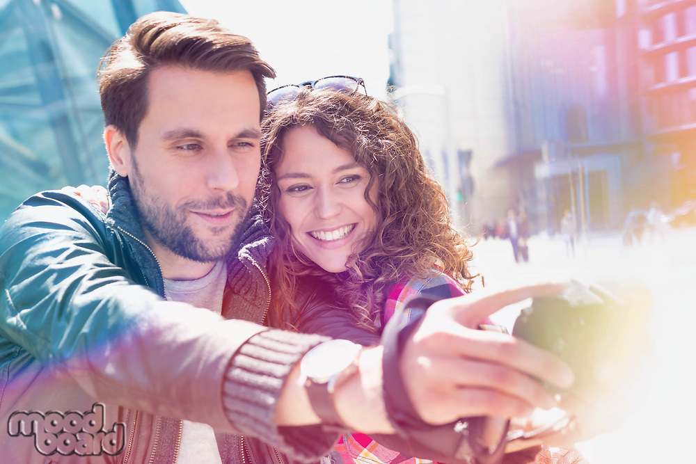 Portrait of young attractive man taking selfie with his girlfriend in the middle of the city with lens flare in background