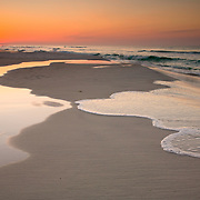 The sun rises over the Emerald Coast of the the Gulf of Mexico waves mimic the shape of the standing water.