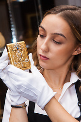 Sotheby's, London, November 21st 2014.  Sotheby's presents one of its strongest offerings of Russian paintings, icons and artworks as the renowned fine art  auction house celebrates its 25th year in Russia. Pictured: A Sotheby's gallery technician displays an Imperial Presentation jewelled gold cigarette case by Faberge, gifted by Emperor Nicholas II.