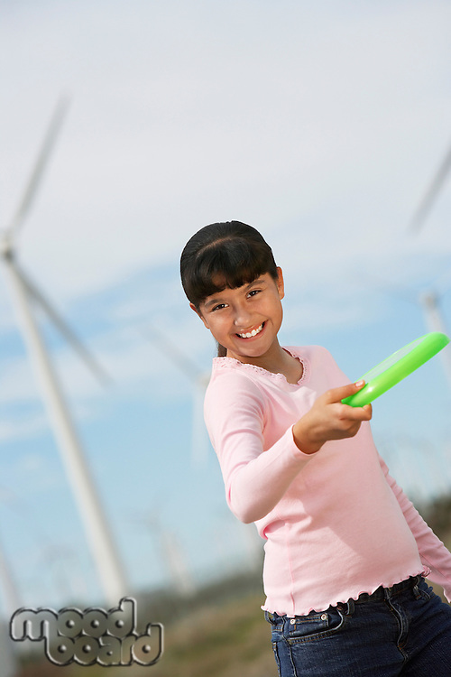 Girl (7-9) throwing disc at wind farm, portrait