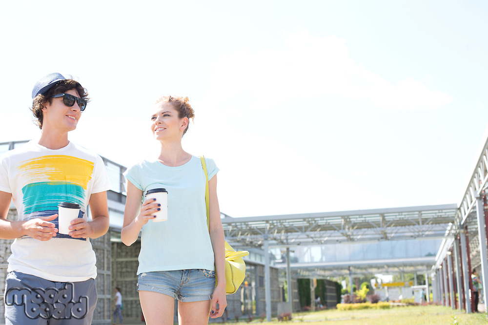 Couple holding disposable cups while walking at park