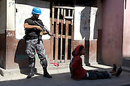 A Jordanian peacekeeper points a machine gun at a Haitian man arrested in the Cité-de-Dieu neighbourhood, an operation criticized by local human rights organizations. Concordia Media Gallery, Montreal, 2010.