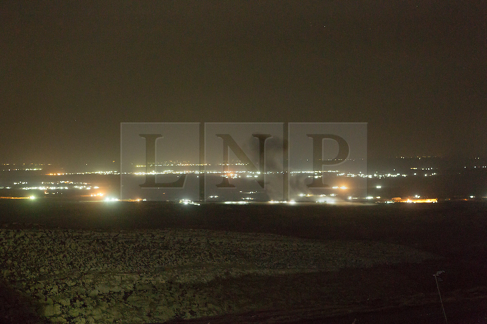 © Licensed to London News Pictures. 01/09/2015. Bashiqa, Iraq. A puff of smoke marks the spot where a coalition aircraft dropped a bomb on ISIS vehicles moving through the town of Bashiqa, Iraq. The ISIS heald city of Mosul can be seen illuminated in the background.<br /> <br /> Bashiqa Mountain, towering over the town of the same name, is now a heavily fortified front line. Kurdish peshmerga, having withdrawn to the mountain after the August 2014 ISIS offensive, now watch over Islamic State held territory from their sandbagged high-ground positions. Regular exchanges of fire take place between the Kurds and the Islamic militants with the occupied Iraqi city of Mosul forming the backdrop.<br /> <br /> The town of Bashiqa, a formerly mixed town that had a population of Yazidi, Kurd, Arab and Shabak, now lies empty apart from insurgents. Along with several other urban sprawls the town forms one of the gateways to Iraq's second largest city that will need to be dealt with should the Kurds be called to advance on Mosul. Photo credit: Matt Cetti-Roberts/LNP