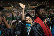Ellenore Holbrook waves to supporters at graduate commencement.  Photo by Ben Siegel