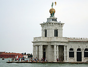 Triangular shaped Punta della Dogana, (the former customs house of the city) separates the Grand Canal and the Giudecca Canal in Venice, Italy. Today it is a centre for contemporary art. The seventeenth-century building. The tower hold a Golden Ball, that is supported by two Atlases;This statue represents Fortune. It was sculpted by Bernardo Falconi