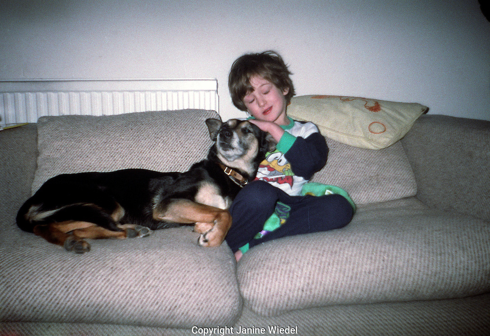 Young male child sitting on sofa with his dog.