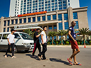 "15 FEBRUARY 2019 - SIHANOUKVILLE, CAMBODIA:  Chinese casino workers walk past Nanhai Pearl Hotel Apartment, a Chinese development in Sihanoukville. There are about 80 Chinese casinos and resort hotels open in Sihanoukville and dozens more under construction. The casinos are changing the city, once a sleepy port on Southeast Asia's ""backpacker trail"" into a booming city. The change is coming with a cost though. Many Cambodian residents of Sihanoukville  have lost their homes to make way for the casinos and the jobs are going to Chinese workers, brought in to build casinos and work in the casinos.      PHOTO BY JACK KURTZ"