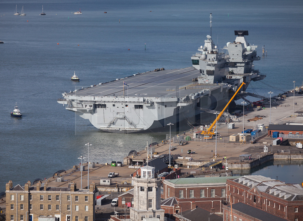 © Licensed to London News Pictures. 25/10/2017. Portsmouth, UK.  Police patrol boats surround HMS Queen Elizabeth alongside in Her Majesty's Naval Base Portsmouth.<br /> <br /> The departure of the Royal Navy's flagship, HMS Queen Elizabeth, from HMNB Portsmouth has been delayed for the second day in a row. The aircraft carrier has been alongside in Portsmouth since 16th August 2017, and was due to sail on Monday 23rd October for the second stages of her sea trials. Her departure was originally delayed due to strong winds, and is now expected to be delayed until Friday at the earliest.<br /> <br /> Flight trials involving the new F-35B Joint Strike Fighter are expected to take place off the coast of the U.S. next year, and she is due to come into service in the early 2020s.  Photo credit: Rob Arnold/LNP