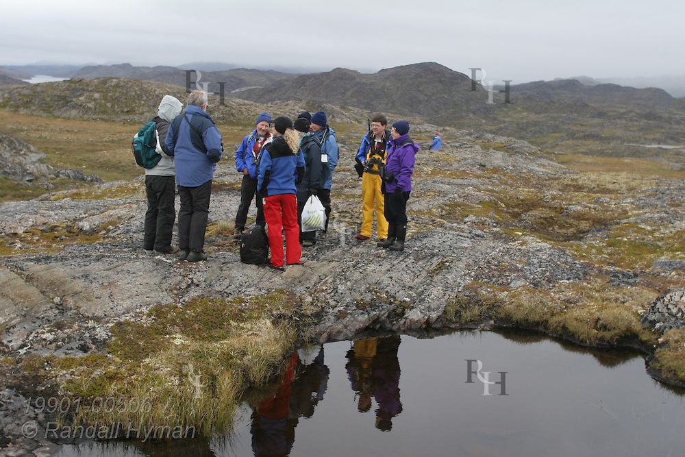 Hikers from small expedtion cruise ship, Clipper Adventurer, gather beside clear pond in the vast rocky landscape of Eqalugssuit, Greenland