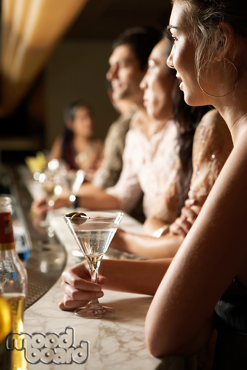 Mid-adult People standing at Bar with cocktail glasses side view