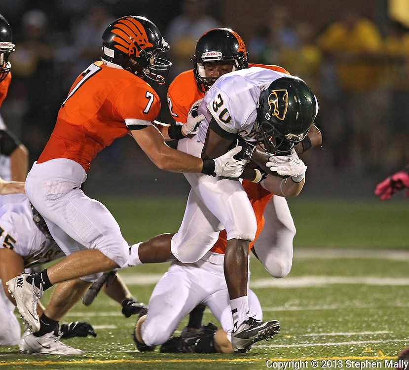 Kennedy's Terrence Hall (30) pulls Prairie's Mitchell Dellamuth (7), Marquan Wilder (42), and Coen Brown (8) for extra yards on a run during their game at John Wall Memorial Stadium at Prairie High School in Cedar Rapids on Friday, September 6, 2013.