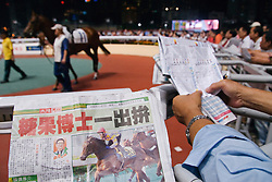 Spectators examine horses in the ring and study the form in newspapers at Happy Valley Racecourse in Hong Kong