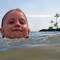 USA, Hawaii, Oahu. A young girl enjoys swimming in the waters of the Kahala Hotel & Resort.
