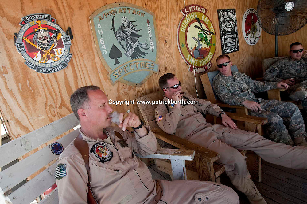 Jalalabad, Eastern Afghanistan: While waiting for their next call Medevac Pilots CW4 Gary Heyne (left)  and Brandon Erdmann enjoy a cigar  on the porch of the Taskforce palehorse Medevac operations centre in Jalalabad. With the fighting increasing during the summer months a busy summer of Medevac operations lies ahead in eastern Afghanistan.