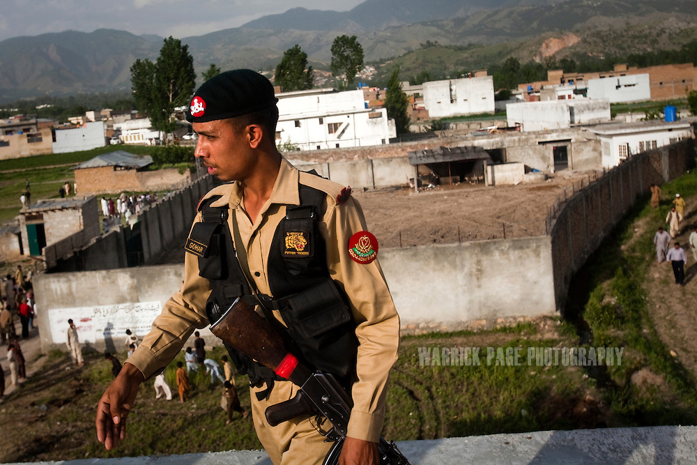 A Pakistani Frontier Constabulary soldier walks atop an adjacent building to the compound where Osama Bin Laden was killed in an operation by US Navy Seals, on May 4, 2011, in Abottabad, Pakistan.  The operation, code-named Operation Neptune Spear, was launched from neighbouring Afghanistan by Seal Team Six. U.S. forces took bin Laden's body to Afghanistan for identification, then dumped it the Arabian Sea. Pakistan has since been widely suspected as having prior knowledge of his whereabouts as the compound was less than a kilometre from the country's biggest military academy. Osama bin Laden was allegedly responsible for supporting the bombing of the US Embassy in Nairobi, Kenya, the attack on the USS Cole and the suicidal attacks of September 11, 2001 in the US. (Photo by Warrick Page)