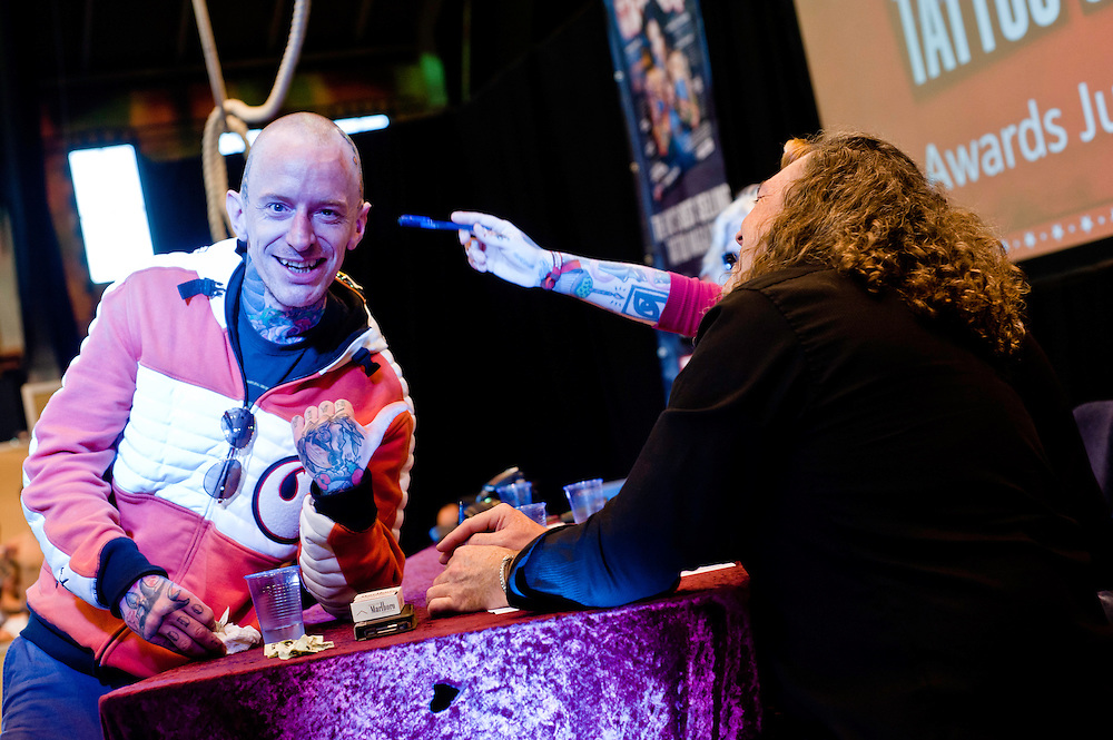 Manchester, UK - 5 August 2012: members of the jury examine a new tattoo for a contest during the Manchester Tattoo Show, one of the most popular conventions of the UK tattoo community.