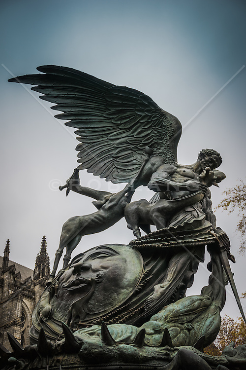 The Peace Fountain is a 1985 sculpture and fountain located next to the Cathedral of Saint John the Divine in the Morningside Heights section of New York City by Greg Wyatt, sculptor-in-residence at the Cathedral. The sculpture depicts the struggle of good and evil, as well as a battle between the Archangel Michael and Satan. The sculpture also contains the Sun, the Moon, and several animals. Although it is called a fountain, there is currently no water on the site. A plaque at the base contains the following inscription:<br />