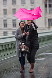 © Licensed to London News Pictures. 03/01/2016. London, UK. Two women struggle to control their umbrella during a gust of wind on Westminster Bridge in London.  London and the UK has experienced heavy rain and wind today. Photo credit : Vickie Flores/LNP