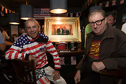 © Licensed to London News Pictures. 13/07/2018. London, UK.  Trump supporter, Ray with Geoffrey pose with a photograph of Donald Trump and Nigel Farage at a Donald Trump special relationship evening and welcome party held at  the Trump Arms Pub (formerly known as Jameson Pub) in Hammersmith, west London. The pub has been decked out with American flags and banners celebrating Donald Trump's arrival in the UK..  Photo credit: Vickie Flores/LNP