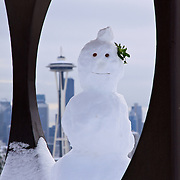Snowman built inside metal sculpture Changing Form by Doris Totten Chase at Kerry Park on Queen Anne Hill, Seattle, Washington