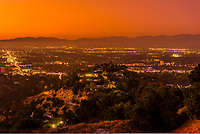 Wide view of the San Fernando Valley with the San Gabriel Mountains behind, shot above Sherman Oaks from Mulholland Drive at twilight, Los Angeles, California USA.