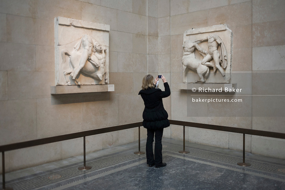 Woman photographs photograpss the Ancient Greek Parthenon Metopes also knows as the Elgin Marbles in the British Museum. 92 Metopes were rectangular slabs placed over the columns of the Athens Parthenon temple depicting scenes from Greek mythology.