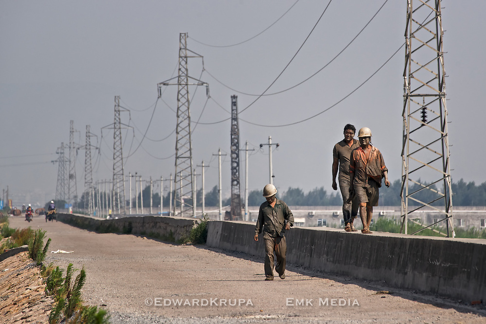 Mud covered men walking near Wenzhou China, by the South China Sea.