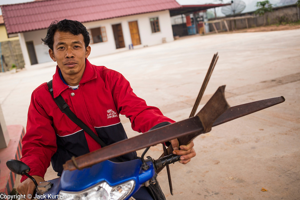 14 MARCH 2013 - LUANG NAMTHA, LAOS: A man holds onto his crossbow while he waits for friends at a gas station in Luang Namtha, Laos. He was going out hunting for bush meat.    PHOTO BY JACK KURTZ