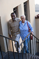 Portrait of senior couple walking up steps, smiling