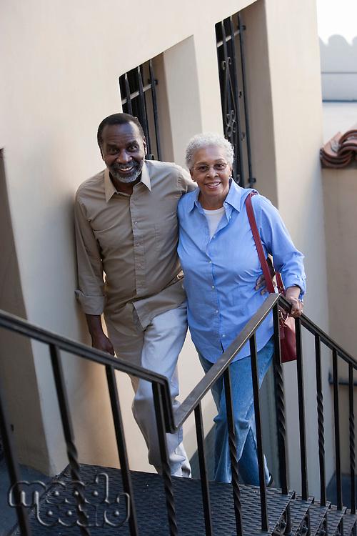 Portrait of senior couple walking up steps, smiling