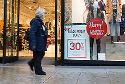 © Licensed to London News Pictures. 24/11/2015. London, UK. A woman walks past a 30% off Black Friday deal sign displayed in a retail shop window in Oxford Street. Photo credit : Vickie Flores/LNP