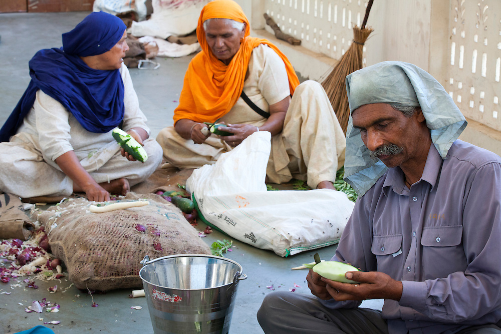Volunteers cut vegetables at a Sikh kitchen in Punjab,India. The sikh kitchen provides ten of thousands of free meals on a daily basis. The main work force at the Sikh kitchen is made of Sikh volunteers.