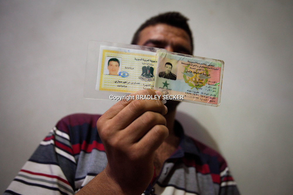 A former Syrian soldier, now FSA fighter, shows his military ID card and a seperate police ID card. During the United Nations mission in Syria the soldier said that all military personnnel were given police ID cards, and answers to the questions they knew the UN would ask. This is an example of how the Syrian regime maintained a huge military presence in urban areas during the United Nations mission, monitoring the implementation of Kofi Annan's six-point-plan. Kastan, Idlib, Syria. 20/06/2012