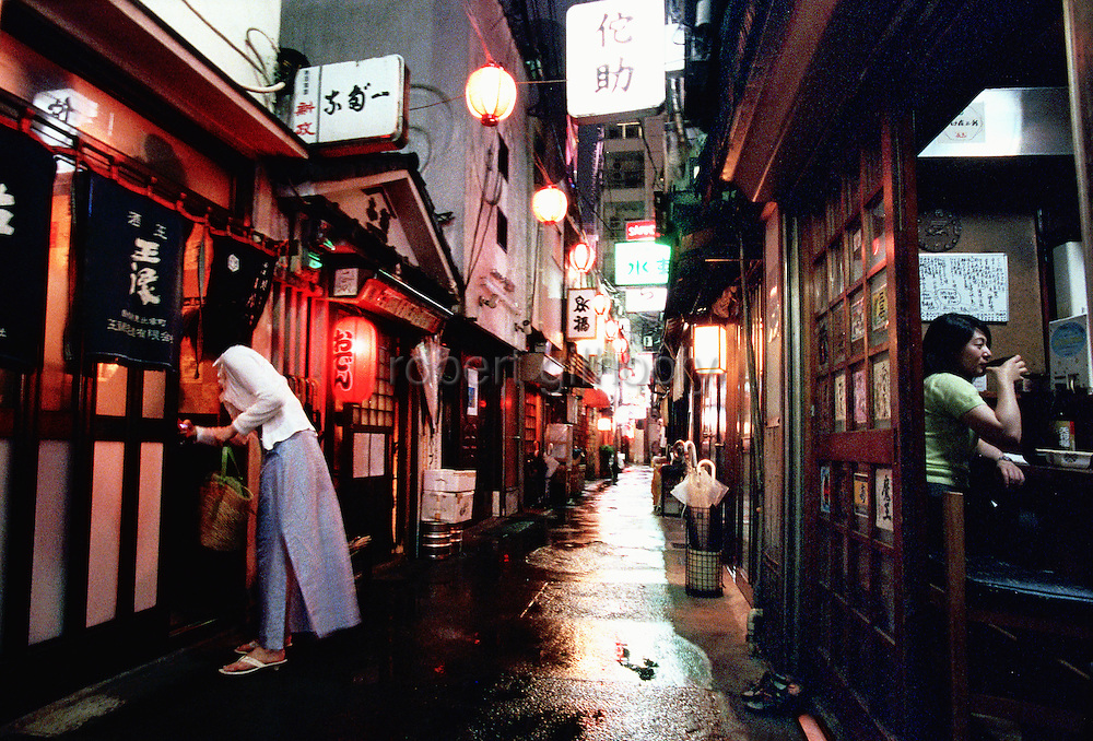 """Some 47 bars and eateries line the narrow alleyways of Nonbeiyokocho, or """"Drunkard's Alley"""", in trendy Shibuya, Tokyo. Nonbeiyokocho began life immediately after World War II as group of tea houses. Though the alley is just a short walk from the central Shibuya shopping district, the rents are low due to the area being built over a river. Today 47 eateries, each with barely enough room to swing a cat, serve beer, fine wines and good, inexpensive fare."""