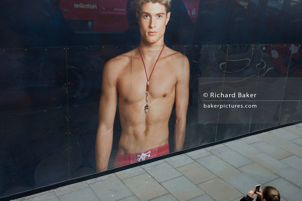 Young woman photographs a giant ad mural of a bare-chested young male model