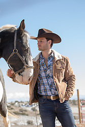 hot cowboy with a Paint horse on a ranch
