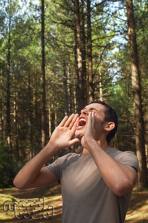 Man standing alone in woods yelling