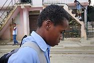 "Robinson Martinez, 15, walks home after school in Santiago, Dominican Repbulic. In the mornings he attends Acción Callejera (Street Action), an organization dedicated to helping child laborers and give them a new purpose in life. Robinson had stopped attending school, but was able to re-enter with the help of Acción. When Robinson first arrived to the center they called him ""zero tolerance,"" because he was so aggressive with the other children that even the slightest touch or taunt made him explode. In a years time he has become affectionate with the staff and has been transformed into a leader. Accion prepares kids to go back to school, provides hot meals for a symbolic fee, field trips, and free medical care and counseling. ""All I had in my heart was an emptiness when I arrived here, now it is full,"" says Robinson. Sara A. Fajardo/Catholic Relief Services"