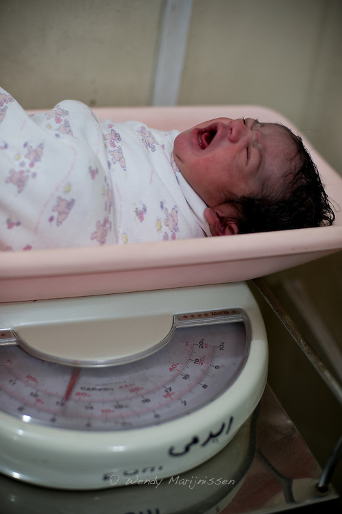 A newborn baby girl is put on the weighing scales after safely being delivered by a c-section in the Edhi clinic. <br /> Run as a charity, the center functions as a buffer between the dai who conduct home deliveries and the hospitals, either private or government run. <br /> Funded solely by private donations, the center offers free services to everyone coming in for help. <br /> Karachi, Pakistan, 2011