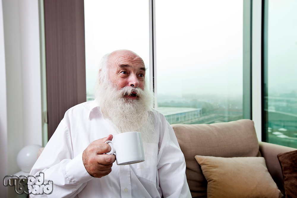 Happy senior man holding coffee cup at home