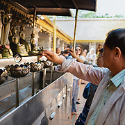 People lighting prayer candles in offering at Wat Doi Suthep, Chiang Mai